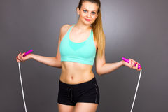 Portrait  of beautiful blonde woman doing exercises with rope. Isolated on gray background Royalty Free Stock Photos
