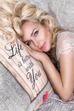 Portrait beautiful blonde woman with a beautiful face and amazing eyes, lies, sleeps on the bed linen in an elegant Stock Images