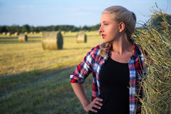 Portrait of beautiful blonde woman in field with haystacks Royalty Free Stock Images