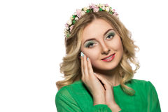 Portrait of a beautiful blonde woman in a green dress that looks into the camera and folded her hands near the face Stock Image
