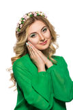 Portrait of a beautiful blonde woman in a green dress that looks into the camera and folded her hands near the face Stock Images