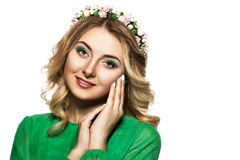 Portrait of a beautiful blonde woman in a green dress that looks into the camera and folded her hands near the face Stock Photography
