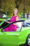 Portrait of a beautiful blonde woman and green sports car Royalty Free Stock Photos