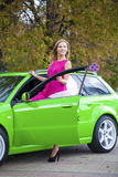 Portrait of a beautiful blonde woman and green sports car Stock Photo