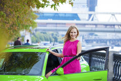 Portrait of a beautiful blonde woman and green sports car Stock Photos