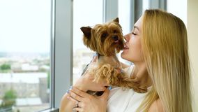 Portrait of beautiful blonde woman holding small fluffy dog kissing her