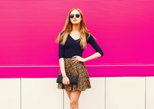 Portrait beautiful blonde woman in leopard skirt, sunglasses with handbag clutch posing. On colorful pink wall background stock photography