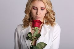 Portrait of the beautiful blonde woman with long blonde hair, perfect skin, keeps the face of a bouquet of red roses flowers, Royalty Free Stock Photos