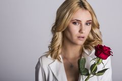 Portrait of the beautiful blonde woman with long blonde hair, perfect skin, keeps the face of a bouquet of red roses flowers,. A sensual and smiling in women`s Stock Photos