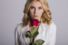 Portrait of the beautiful blonde woman with long blonde hair, perfect skin, keeps the face of a bouquet of red roses flowers,. A sensual and smiling in women`s Stock Photography