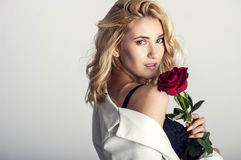 Portrait of the beautiful blonde woman with long blonde hair, perfect skin, keeps the face of a bouquet of red roses flowers, Royalty Free Stock Image