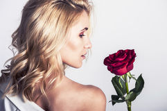 Portrait of the beautiful blonde woman with long blonde hair, perfect skin, keeps the face of a bouquet of red roses flowers, Royalty Free Stock Photo