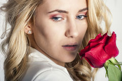 Portrait of the beautiful blonde woman with long blonde hair, perfect skin, keeps the face of a bouquet of red roses flowers, Stock Photography
