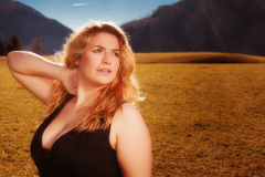 Portrait of a beautiful blonde woman with luscious cleavage. In black tank dress. Illuminated on a meadow, the Alps in the background of the autumn sun royalty free stock photography