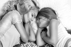 Portrait of the beautiful blonde woman mother and daughter on the beautiful face and amazing eyes lie sleeping on a bed in an eleg Royalty Free Stock Images