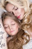 Portrait of the beautiful blonde woman mother and daughter on the beautiful face and amazing eyes lie sleeping on a bed in an eleg Stock Images