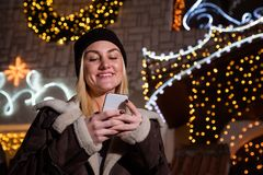 Portrait of beautiful blonde woman using smart phone in front of. House decorated with Christmas lights. Winter and holidays concept Royalty Free Stock Photo