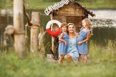 Portrait of beautiful blonde woman walking with two daughter near lake at sunset royalty free stock images