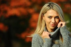 Portrait of beautiful blonde woman wearing cozy sweater in the park. Portrait of beautiful blonde woman wearing cozy sweater during the autumn in the park Royalty Free Stock Image