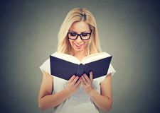 Portrait of beautiful young woman wearing glasses reading a book stock image
