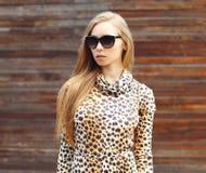 Portrait of beautiful blonde woman wearing a leopard dress and sunglasses Stock Image