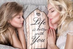 Portrait of the beautiful blonde woman mother and daughter on the beautiful face and amazing eyes lie sleeping on a bed in an eleg Royalty Free Stock Photography