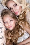 Portrait of the beautiful blonde woman mother and daughter on the beautiful face and amazing eyes lie sleeping on a bed in an eleg. Portrait of the beautiful royalty free stock photo