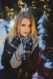 Beautiful blonde young caucasian woman in black coat and scarf Stock Image