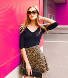 Portrait beautiful blonde young woman in leopard skirt, sunglasses with handbag clutch posing on city street. Over colorful pink wall background royalty free stock image