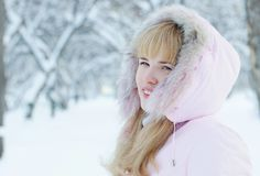 Portrait of a beautiful blonde young woman outdoors in winter. Portrait of a beautiful blonde young woman outdoors in a winter forest Stock Images