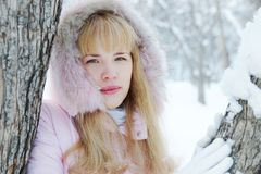 Portrait of a beautiful blonde young woman outdoors in winter. Portrait of a beautiful blonde young woman outdoors in a winter park Royalty Free Stock Photography