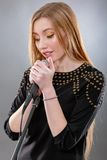 Portrait of a beautiful blonde young woman singing into micropho Royalty Free Stock Photography
