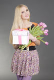 Portrait of beautiful blondie girl with gift and flowers Stock Photos