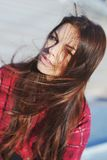 Portrait of a beautiful blue-eyed girl with long silky, disheveled by the wind,  hair in red plaid shirt. Closeup. Stock Photo