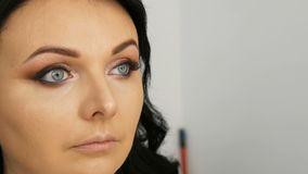 Portrait of a beautiful blue-eyed woman model with long black hair who is doing evening brown eye makeup and eyebrow stock video