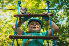 Portrait of a beautiful boy of eleven years in a blue helmet climbing a ladder in a rope park in the summer stock image
