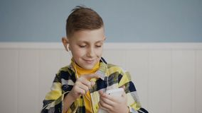 Portrait. A beautiful boy is listening to music from the phone in the earphones cheerfully dancing at house. On the. Portrait. A beautiful blonde boy is stock footage