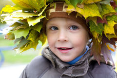 Portrait of beautiful boy in wreath from leaves Royalty Free Stock Image