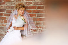 Portrait of a beautiful bride against brick wall stock image