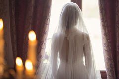Portrait of the beautiful bride against a window indoors Royalty Free Stock Image