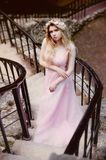 Portrait of a beautiful bride blond girl in pink lace dress ,hair decoration, handmade. Tenderness.Is long old stairs stock images
