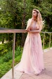 Portrait of a beautiful bride blond girl in pink lace dress ,hair decoration, handmade. Tenderness. Standing in the Royalty Free Stock Photos