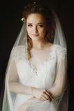 Portrait of beautiful bride, blonde bride in elegant white weddi. Ng dress with veil posing in dark room, emotional face closeup. amazing tender romantic moment Stock Image