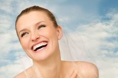 Portrait of beautiful bride with blue sky in background. The beutiful bride is smilling and happy Royalty Free Stock Images