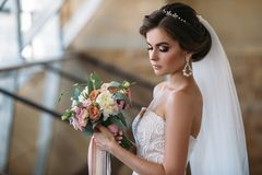 Portrait of beautiful bride with bouquet flowers in white luxury dress. Gorgeous model with bridal makeup and hairstyle stock image