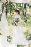 Portrait of beautiful bride with bouquet in the nature. fine art photography. Royalty Free Stock Images