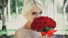 Portrait of a beautiful bride with a bouquet of red roses in her hands. stock photography