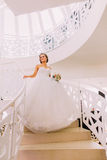 Portrait of beautiful bride with bouquet walking down the stairs indoors Royalty Free Stock Photos
