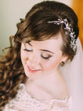 Portrait of a beautiful bride with bright makeup and curly hairstyle closing eyes Stock Photography