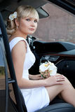 Portrait of a beautiful bride in a car with a bouquet of flowers. Stock Images